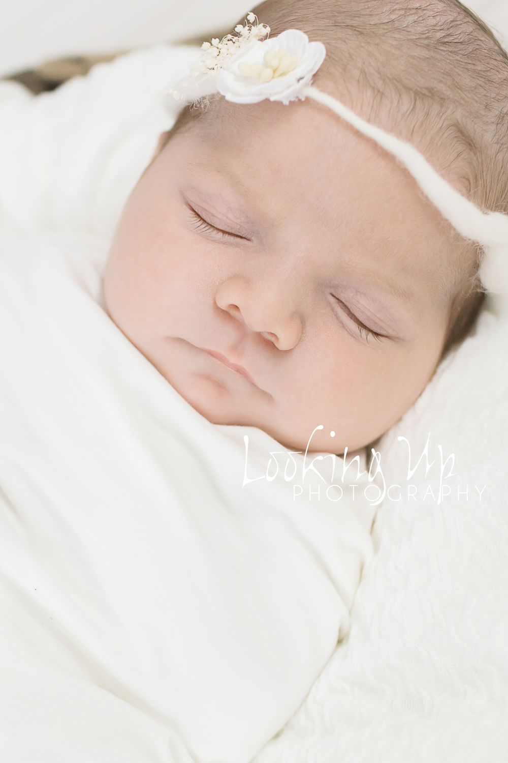 adorable baby girl sleeping in all white