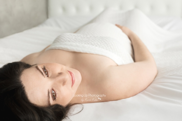 Expectant Mommy posed on bed with delicate white fabric for glamor maternity portrait session