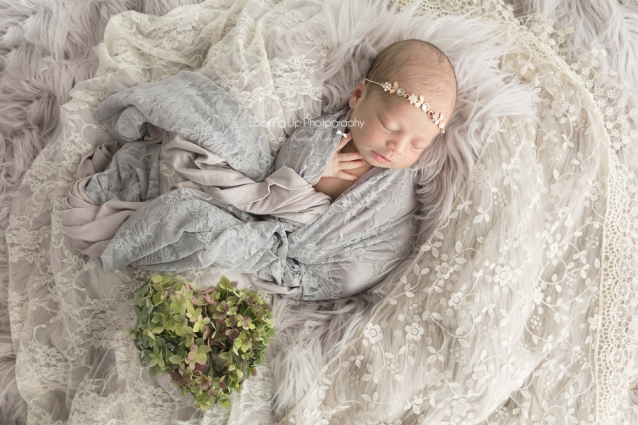 Sleeping beauty baby girl wearing flower crown and wrapped in neural tones of lace with gray fur for newborn session baby portrait