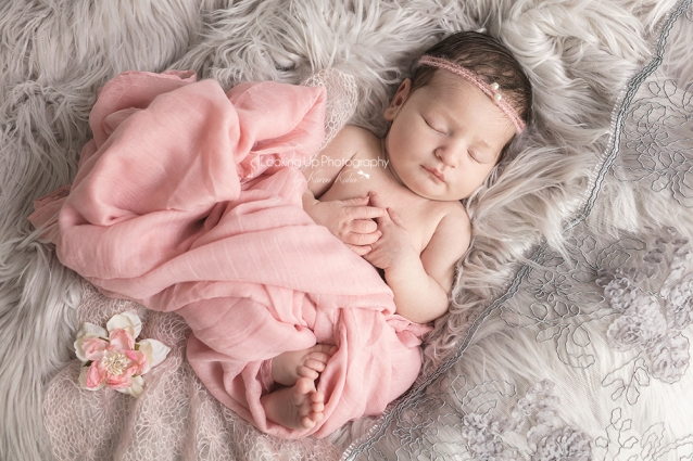 Sleeping newborn adorned in pink fabric and pearl headband surrounded by gray lace and cozy fur with gentle hands posed for baby girl portrait session