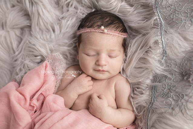 Newborn portrait with smiling baby dressed in soft pink fabric and pearl headband with gray lace and cozy fur and tiny hands posed for baby girl session
