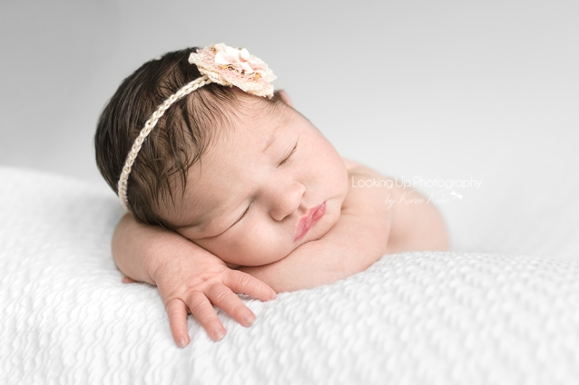 Sleepy baby girl posed reclining on arms with lovely hair and flower headband and pouty lips on white blanket for newborn portrait session