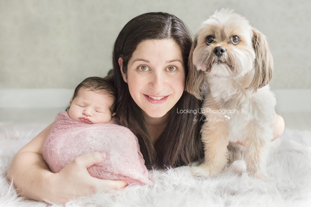 Adorable pet dog with mommy and newborn cuddling with sweet pink lace wrap for baby girl portrait session
