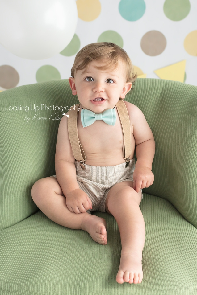 One year old baby boy wearing bow tie and suspenders smiling in snazzy green chair and polka dots for 12 month milestone portrait cake smash session