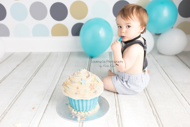 12 month old baby boy donning bow tie and suspenders eating cake in stylish blues and grays and polka dots for cake smash session 1 year milestone portrait