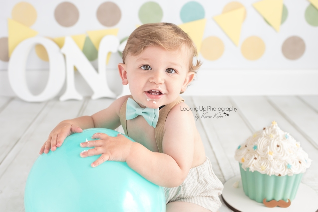 12 month celebration for baby boy looking snazzy in bow tie and suspenders with polka dots and mustache cake for One year old milestone portrait cake smash session