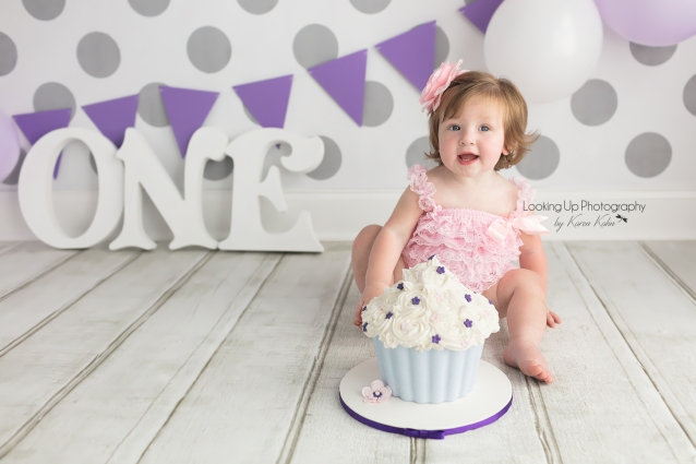 Pretty in pink 12 month milestone for baby girl looking sweet in lace and flower hair bow with gray polka dots for cake smash session one year old portrait