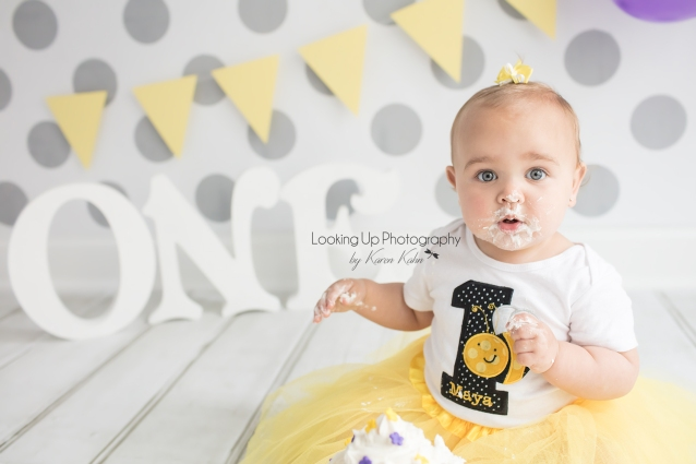 Bumble bee theme one year old milestone for baby girl looking adorable in yellow and white with gray polka dots for cake smash session 12 month old portrait