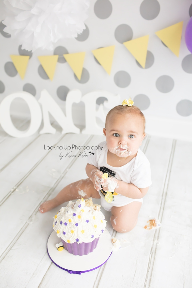Cake smash session with bumble bee theme for one year old milestone baby girl looking adorable in yellow and white with gray polka dots for 12 month portrait