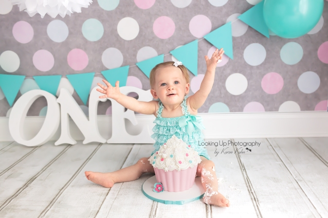 Green and pink themed cake smash session for one year old milestone baby girl looking sweet in lace with polka dots for 12 month portrait