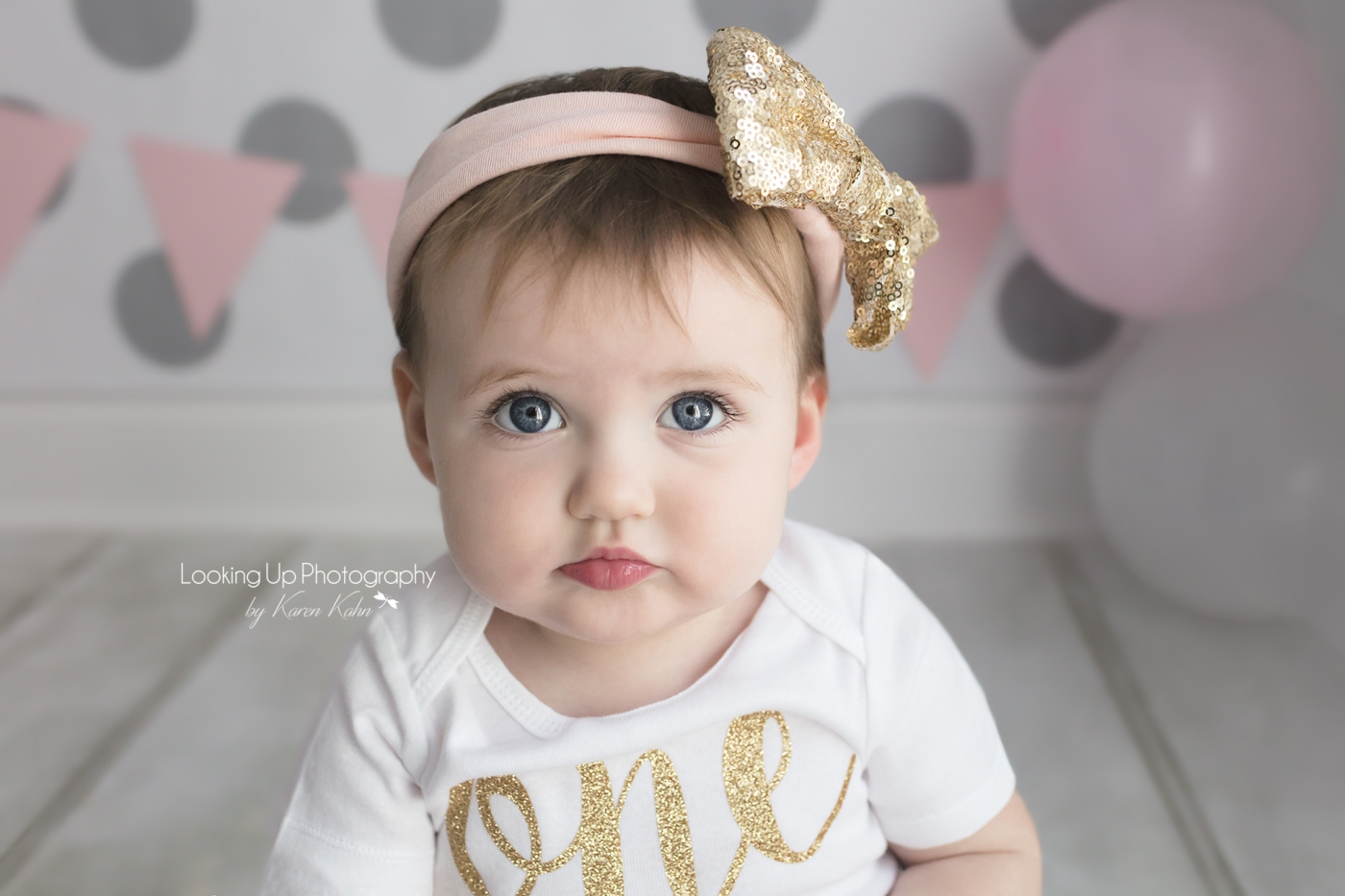 Pouty cuteness in gold and pink themes themed cake smash session for one year old milestone baby girl looking adorable in onesie with gray polka dots for 12 month portrait