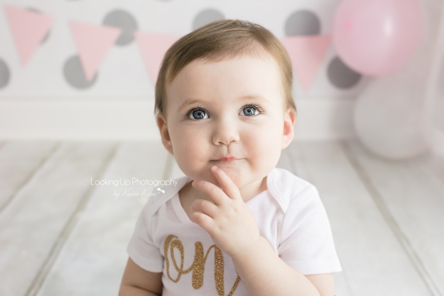Thoughtful pose and big blue eyes in gold, pink and white cake smash session for one year old milestone baby girl looking sweet with gray polka dots for 12 month portrait