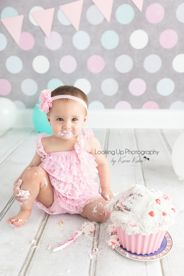 Pink lace for adorable 12 month milestone for baby girl looking sweet with gray polka dots for cake smash session one year old portrait