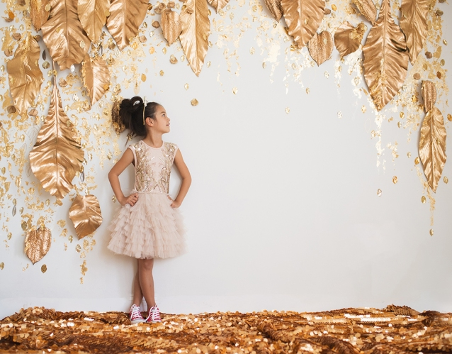 Fall holiday portrait session with girl with golden dress and red sneakers in festive Joyful Gatherings gold set design