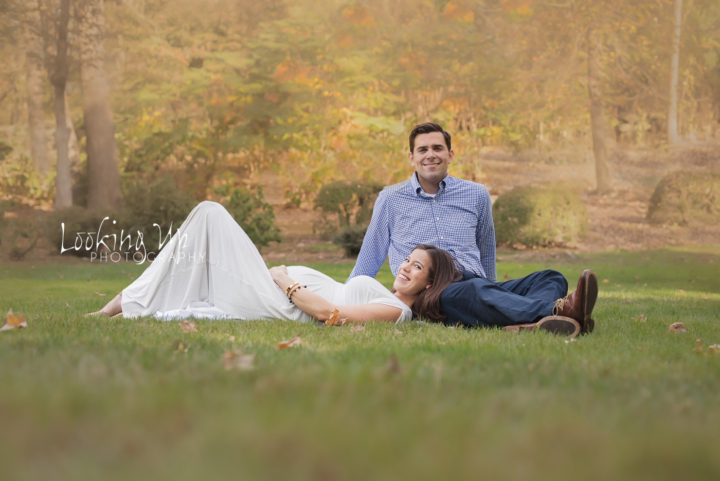 Expecting mom and dad relaxing in the grass with beautiful yellow fall colors for outdoor posed maternity session