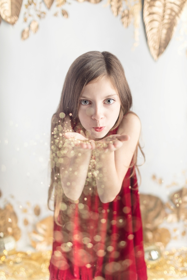 Girl with long hair and big eyes and festive red dress blowing glitter in the air in whimsical Joyful Gatherings gold set design for fall holiday portrait session