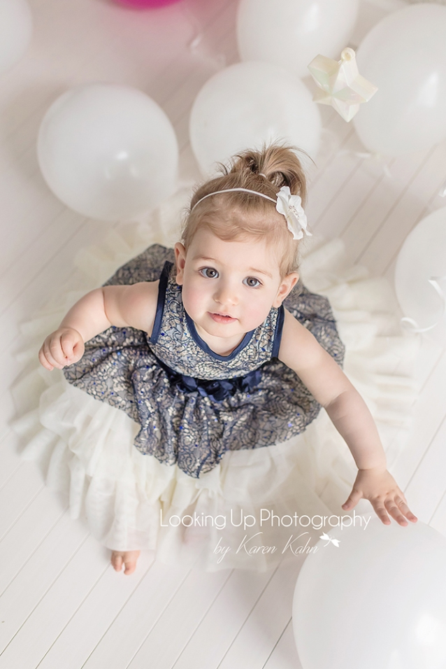 Baby girl in blue lace dress and white balloons for 12 month milestone 1st birthday portrait session