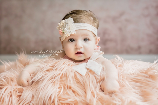Baby girl with peach fuzzy blanket and white lace flower and pearl headband for 4 month milestone portrait session