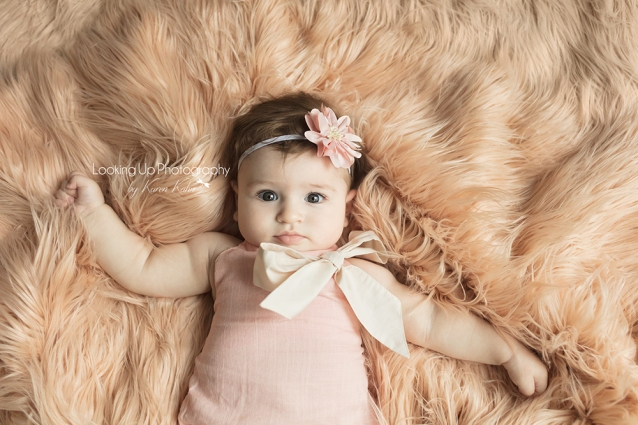 Portrait session aerial view of baby girl laying on peach fuzzy blanket and pink flower headband for 4 month milestone
