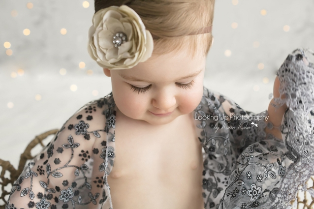 9 month old baby girl in gray lace and flower headband with sparkles for milestone portrait session