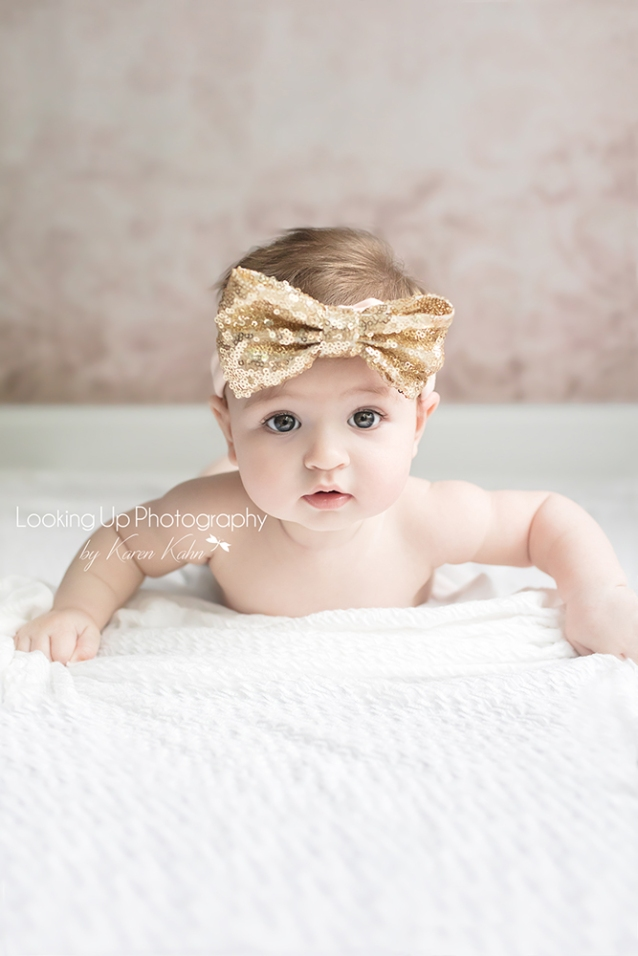 4 month milestone portrait session of baby girl laying on her stomach with gold glitter bow headband and pink backdrop