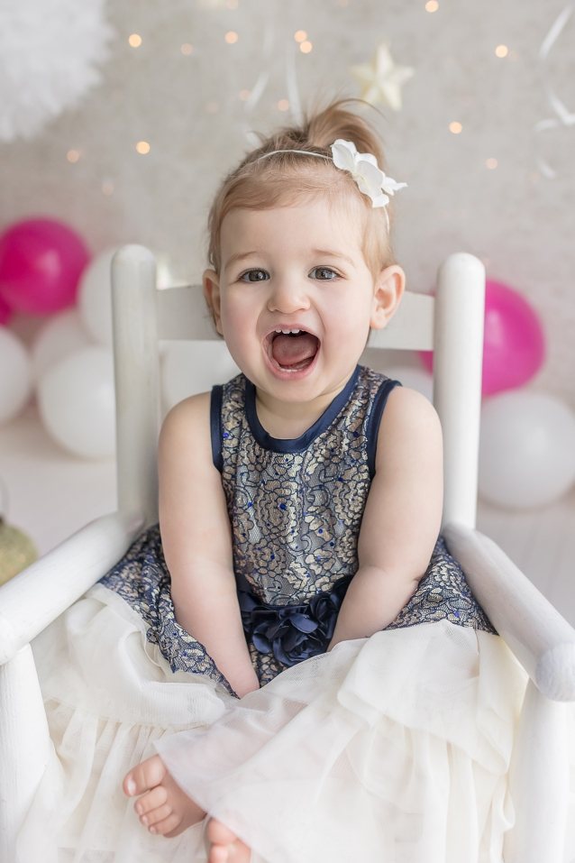 Laughing 12 month old baby girl in blue lace dress and pink and white balloons for 1st birthday milestone portrait session