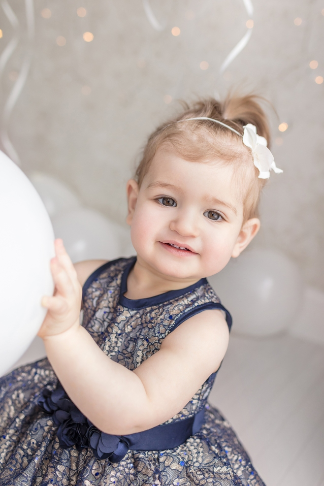 1st birthday milestone portrait session with happy 12 month old baby girl in blue lace dress and white balloons and sparkle