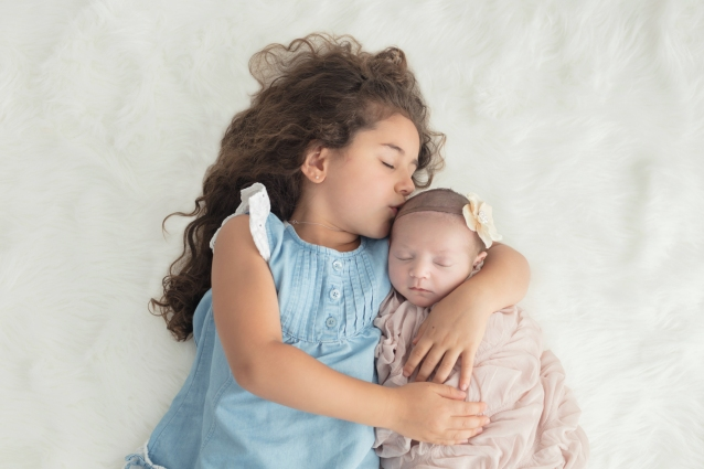 Big sister kissing new little sister with white flower headband swaddled in champagne wrap for baby girl's newborn portrait session