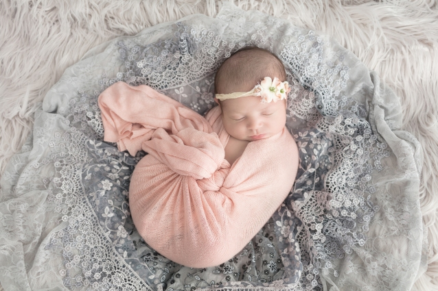 Newborn portrait session of baby girl with peach and white flower headband swaddled in peach wrap surrounded by gray lace and gray fur