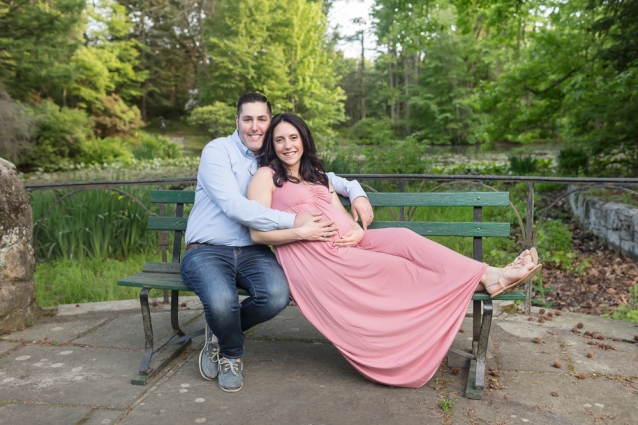 Smiling expecting mom in pink and dad lounging on bench enveloped in gorgeous green spring colors for posed outdoor maternity session