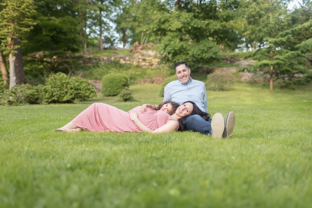 Posed outdoor maternity session with happy expecting mom in pink, big-sister-to-be, and dad lounging on grass in a beautiful field of trees with green spring colors