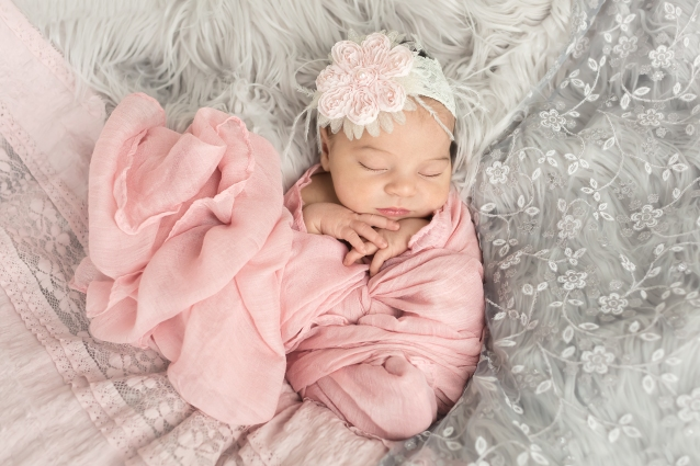 Baby girl swaddled in a pink wrap shaped like a heart and a gorgeous pink and white flower headband peach surrounded by gray and pink lace and gray fur for a Newborn portrait session