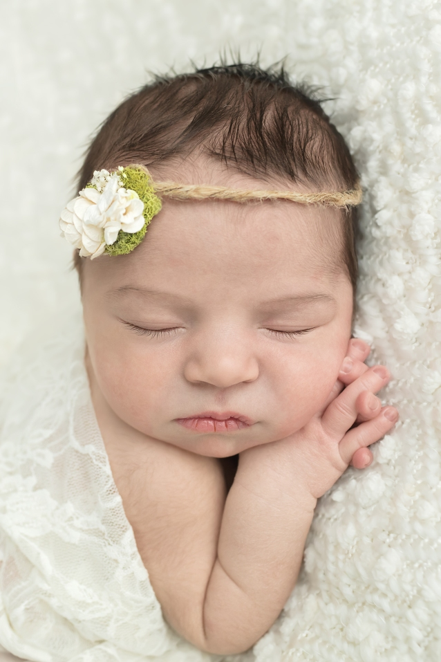 Posed newborn portrait session of baby girl on cream blanket with white flower headband with close up of hand clasped and adorable face
