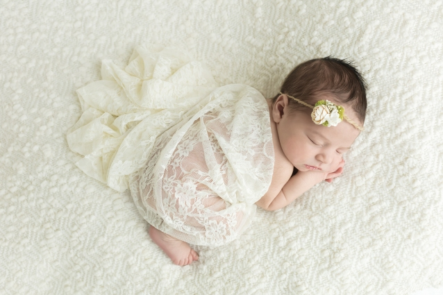 Sleeping baby girl posed wrapped in cream lace on cream blanket with white flower headband for newborn portrait session