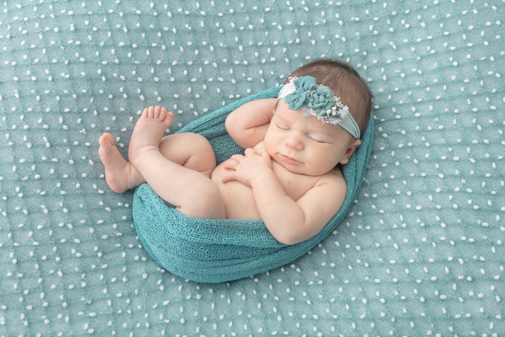 newborn photography, newborn girl swaddled in a dusty teal wrap, dusty teal newborn floral headband, dusty teal newborn blanket