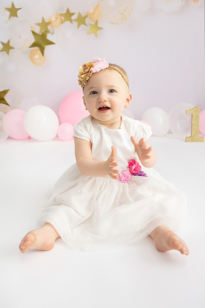 one year-old wearing an ivory tulle dress and clapping her hands, 1st birthday cake smash session