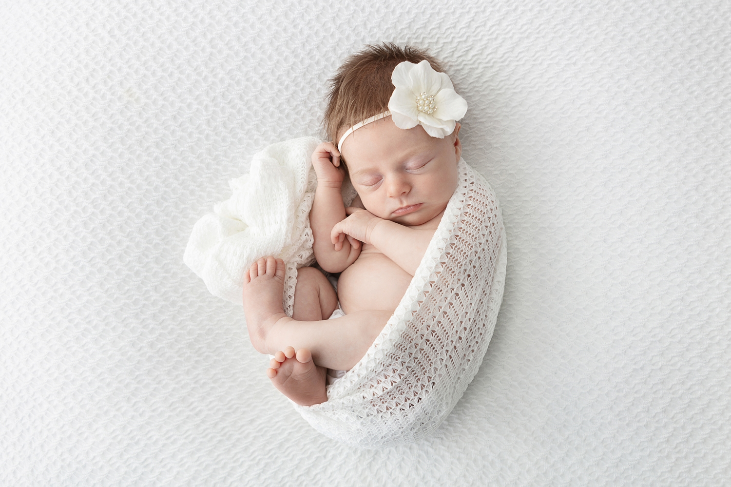 sleeping newborn with a head full of red hair wrapped in an open knit ivory blanket on a woven white background, baby wearing a big white flower headband with pearl flower center