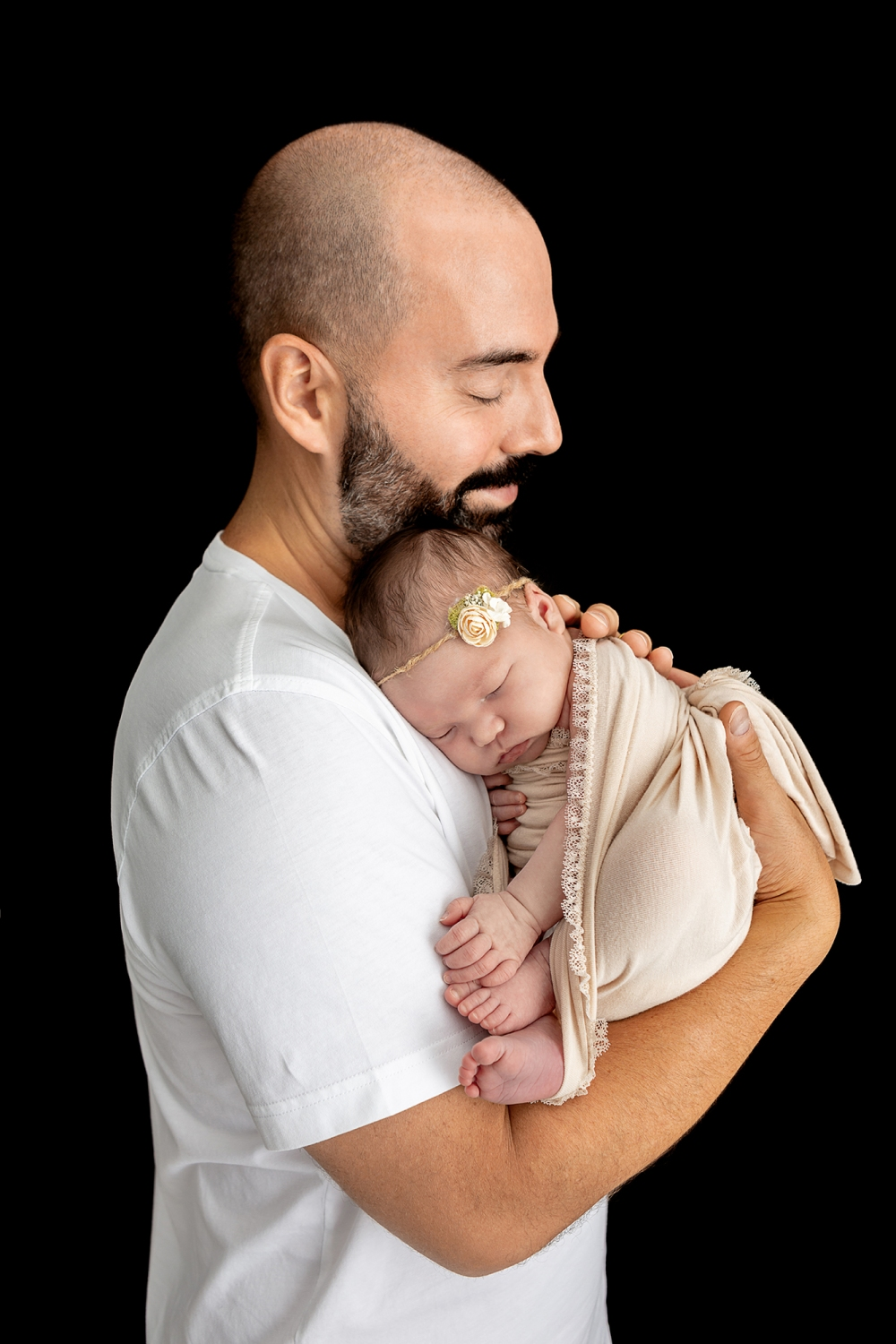 father with a salt and pepper beard wearing a white tee closing his eyes and smiling as he holds his newborn daughter who is wearing a twine and rosette headband and wrapped in an off-white stretch wrap with lace trim, the image is contrasted by a black background