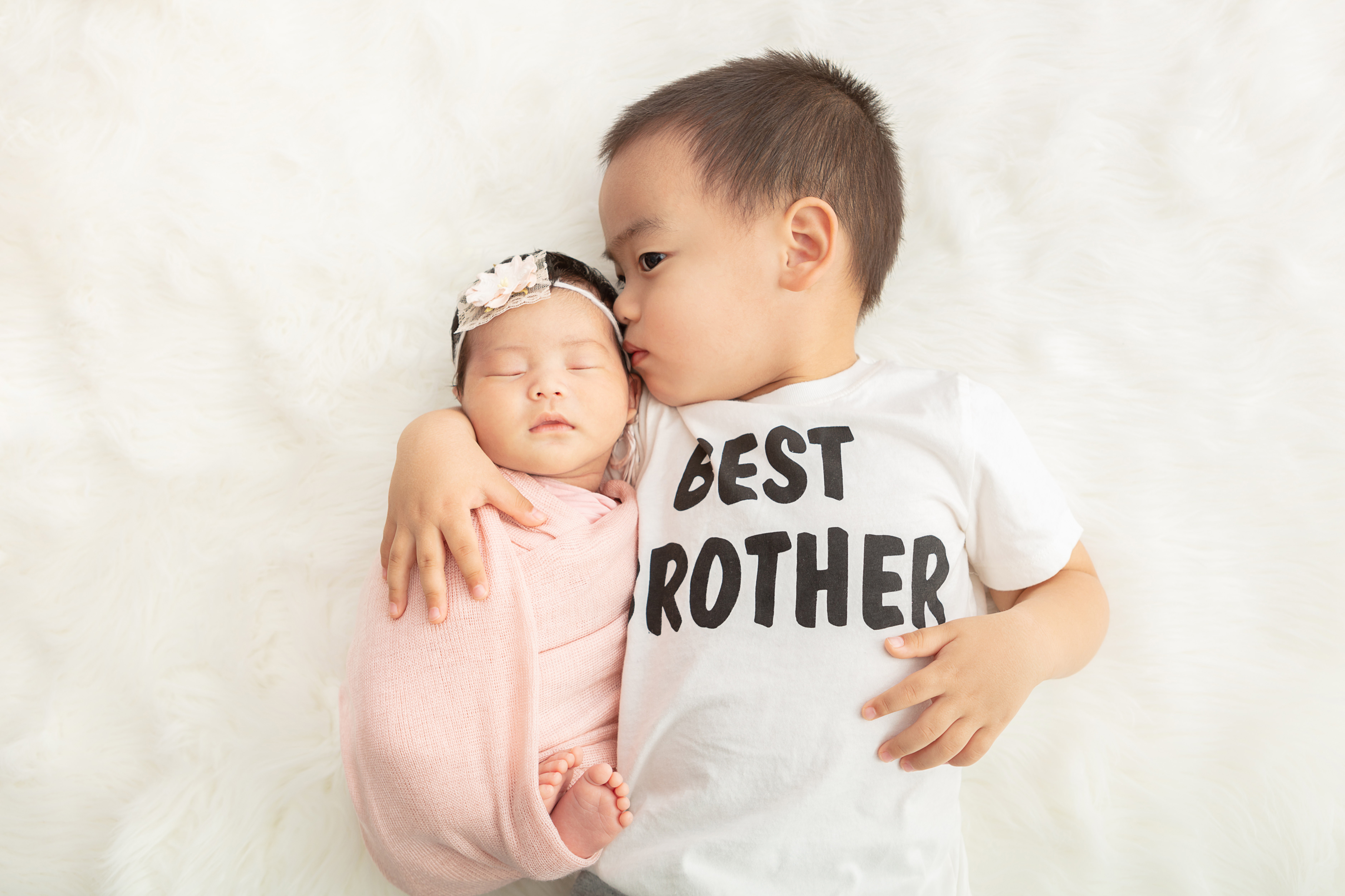 toddler boy wearing a best brother t-shirt and snuggling his newborn baby sister who is wrapped in a peachy pink swaddle