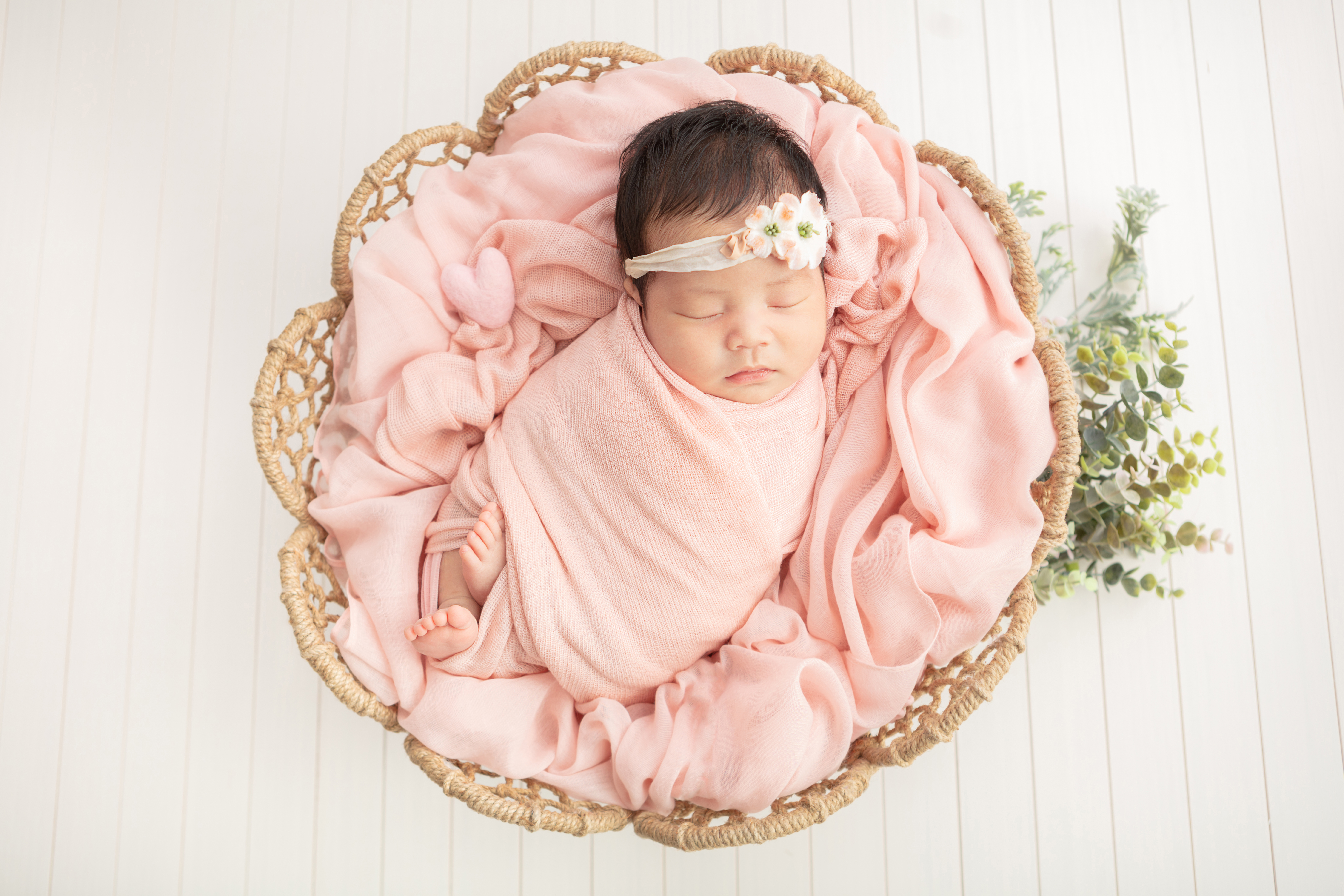 newborn baby girl with dark hair, swaddled in a light peachy pink swaddle, in a flower shaped wicker basket