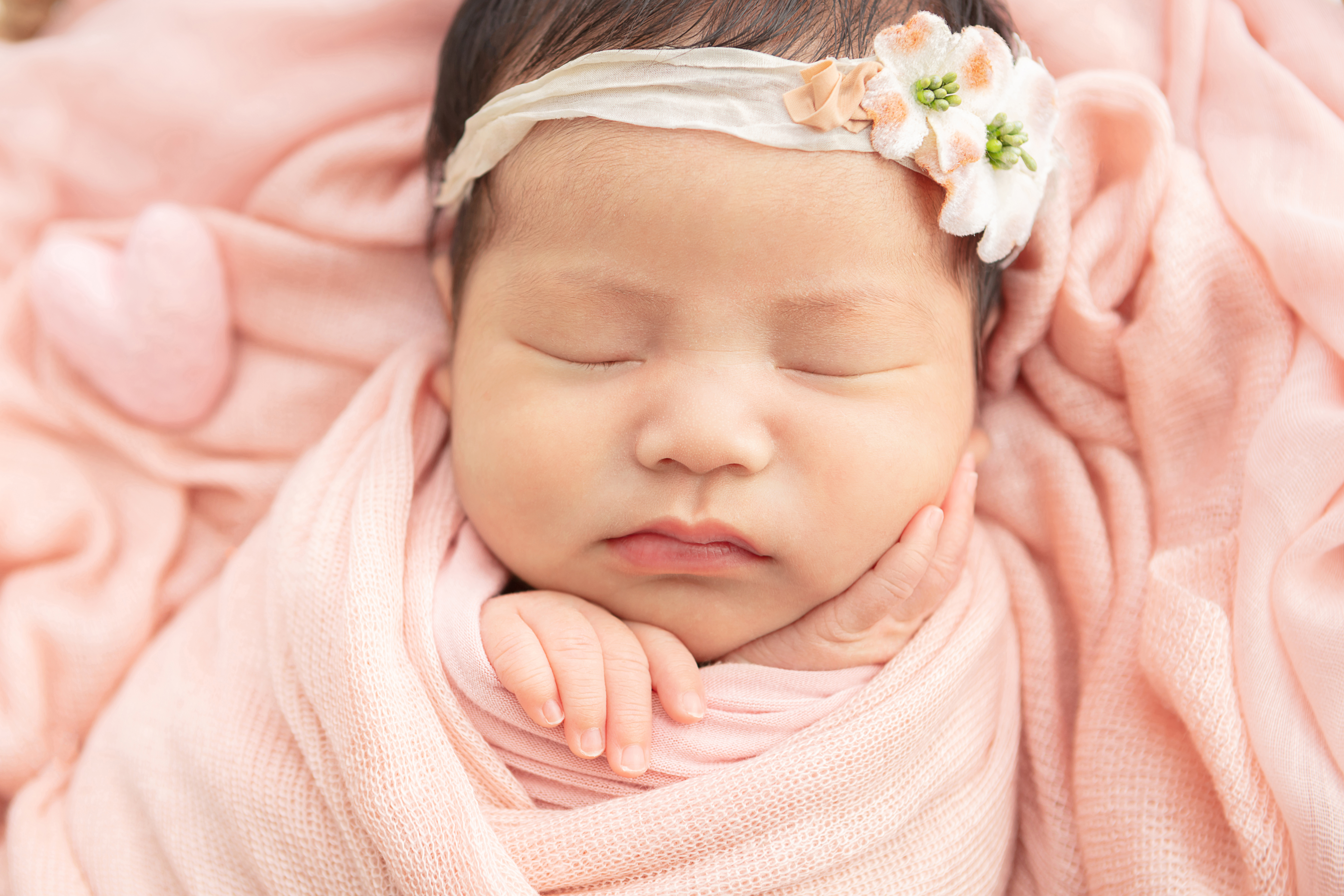 sweet newborn baby girl wearing a muslin floral headband, with her hands delicately tucked in a peachy pink swaddle blanket