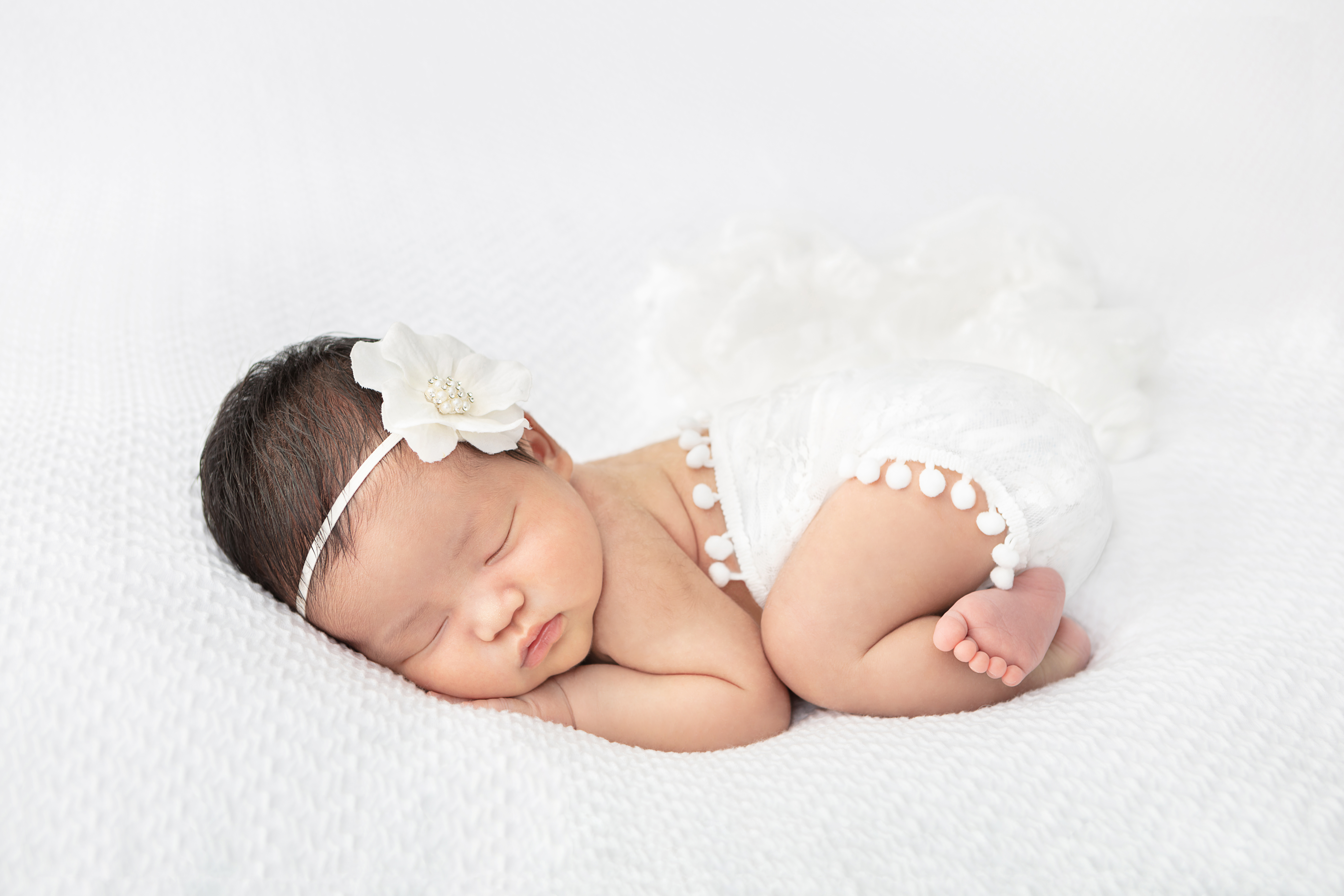 sweet newborn baby girl wrapped in a white swaddle with pom poms and lying on a white textured blanket