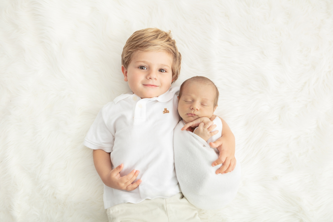 proud toddler brother with his arm around his new baby brother