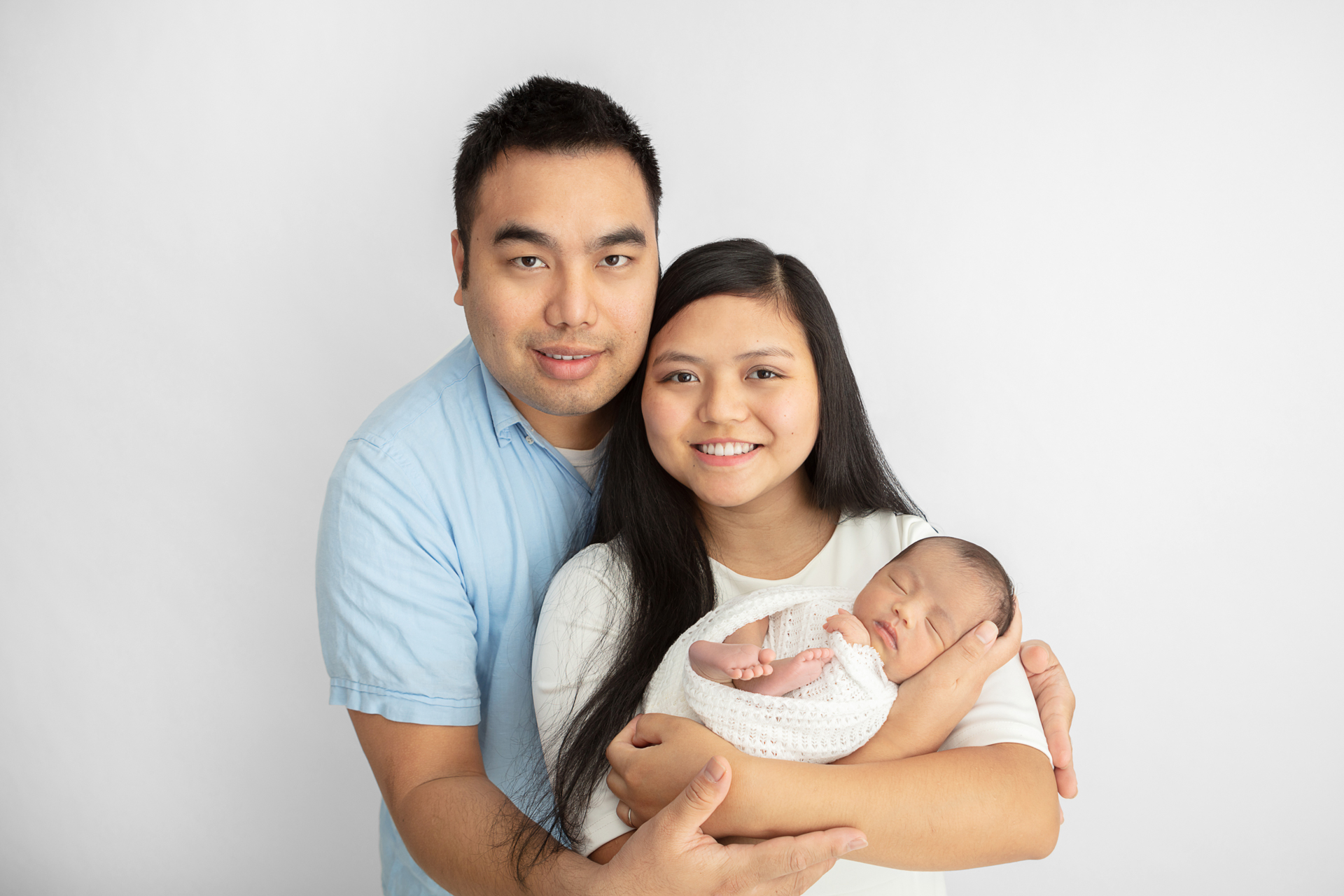 new family of three; new parents smiling at the camera; mom holding her newborn daughter as dad wraps his arms around his girls