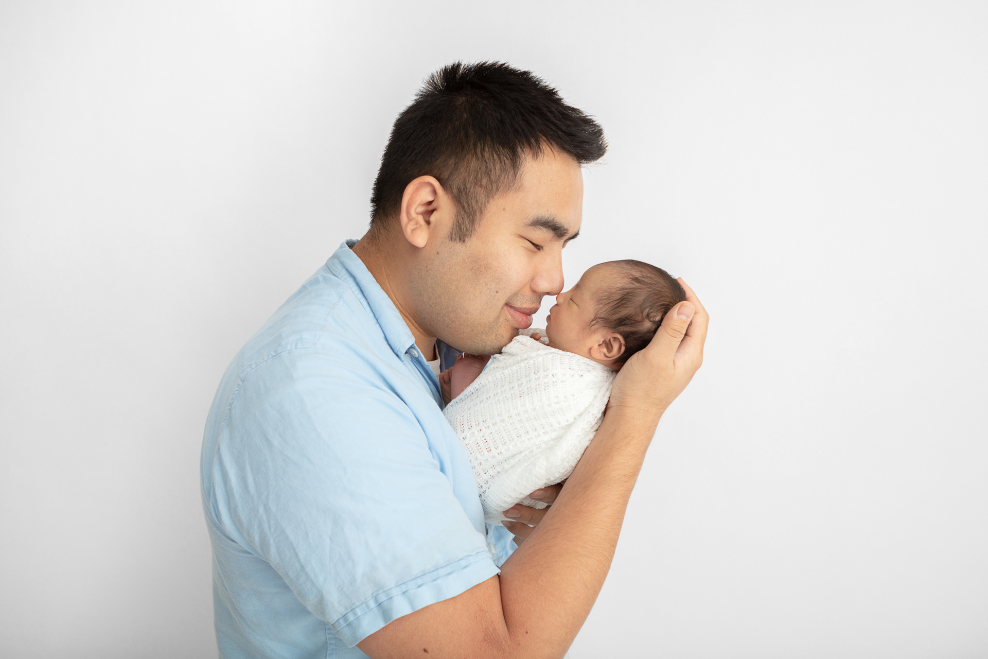 father with dark hair touching noses with his newborn baby girl who is wrapped in a white waffle weave blanket