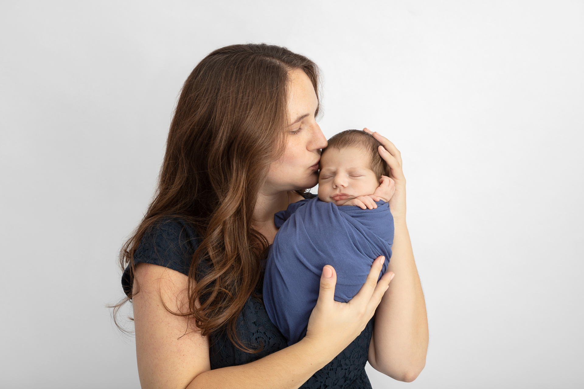 mom with long auburn hair wearing a navy top holding her newborn baby kissing them