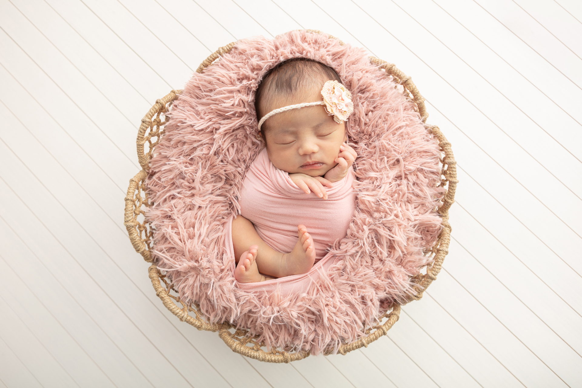 newborn baby girl with dark hair who is wrapped in a dusty pink swaddled, snuggled in a wicker basket with a dusty pink flokati, against a white wood paneled background