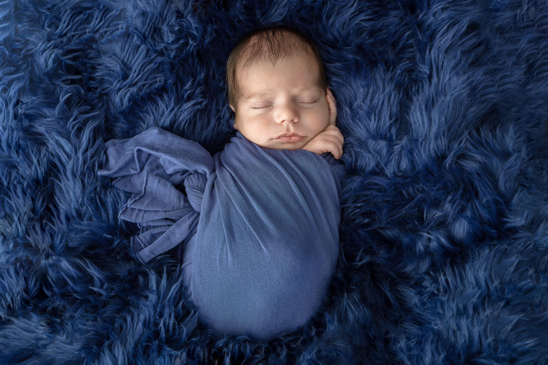 newborn baby boy swaddled in lightweight navy swaddle on a navy flokati