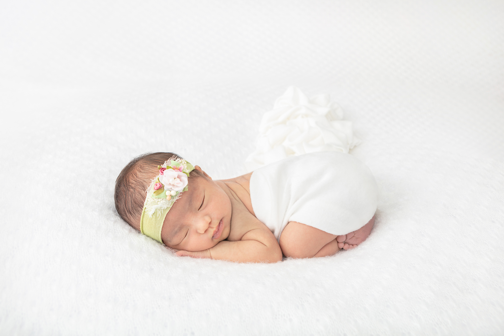 newborn baby girl with dark hair wearing a lime green stretchy headband with white and pink florals
