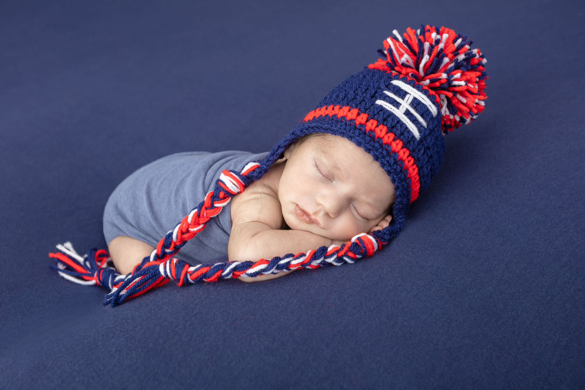 New England Patriots inspired newborn photo; sleeping baby boy wearing a Patriots red, white, blue stocking cap